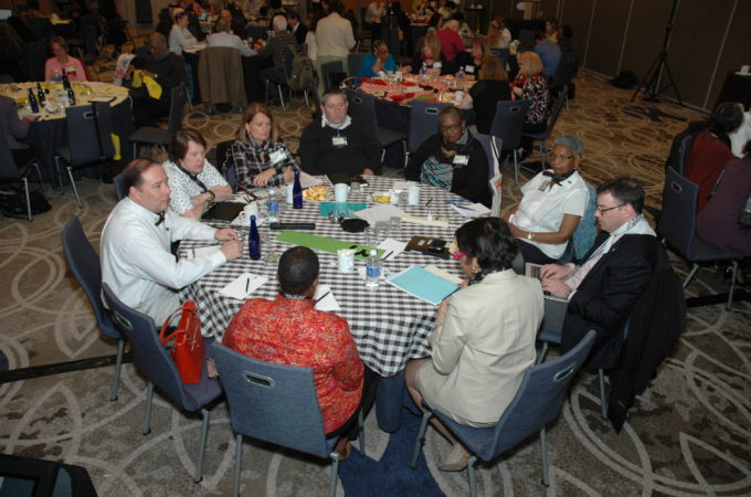 Photo of group gathered around table having a discussion