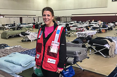A female woman wearing a Red Cross vest stands among cots in a gymnasium being used as a temporary shelter.