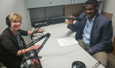 photo showing Mary Jo Monahan and Angelo McClain sitting at a desk with microphones in a recording studio.